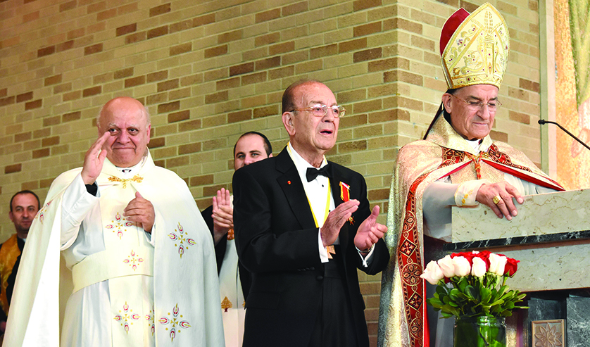 Chorbishop Louis Baz, left, waves to his congregation at St. Maron Catholic Church in Detroit after being elevated to his new rank by Maronite Patriarch Cardinal Bechara Peter Rai during the patriarch's visit to Detroit. In the middle is Dr. Daher Rahi, a relative of the patriarch who lives in southeast Michigan.